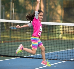 Girl running on tennis court.