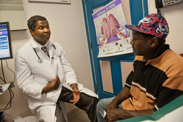 A doctor talks to a patient in an exam room.