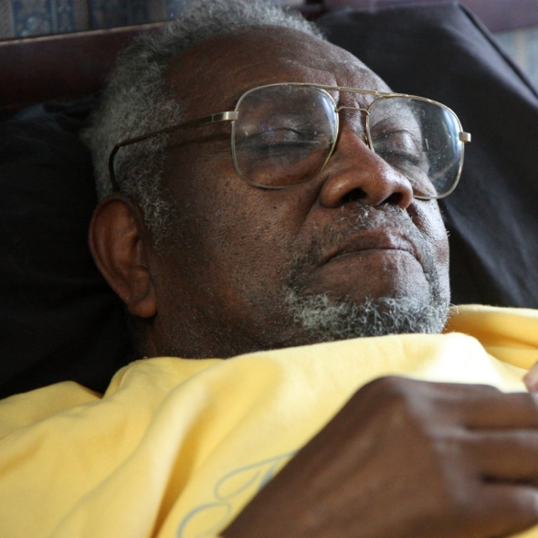 An older man asleep on a bed.