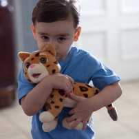 A young boy holds a stuffed toy.