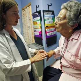 A doctor checks an elderly patient's hand during an examination.