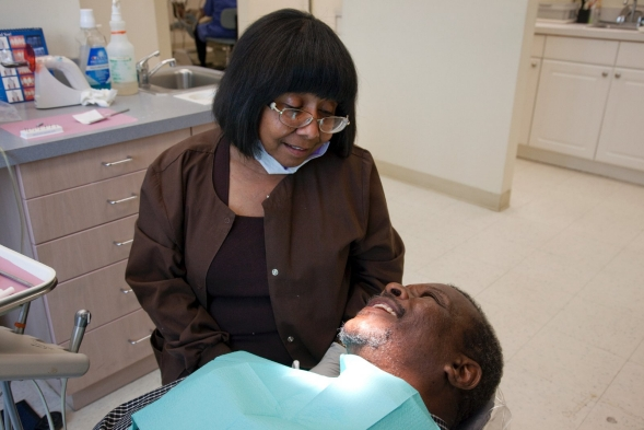 A dental assistant talks to a patient waiting to recieve treatment.