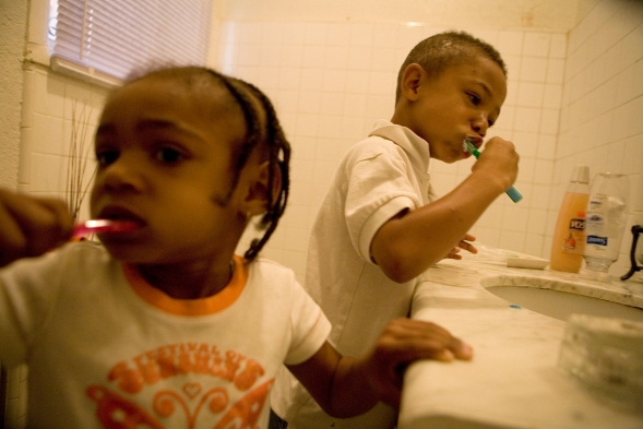 A sister and brother cleaning their teeth in their bathroom.