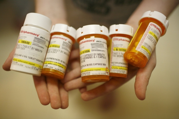 A person holds several bottles of prescription medicine.