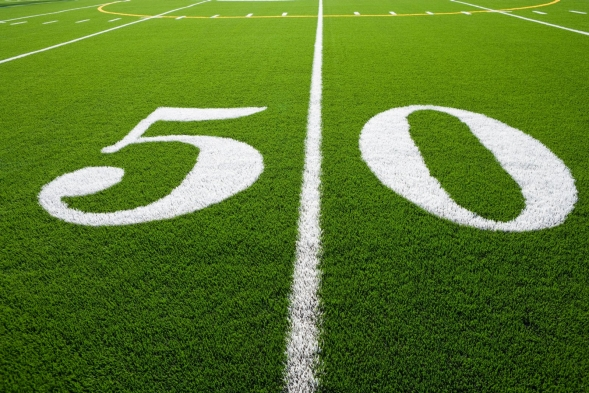 The fifty yard line on football field. used to represent fifty percent of reaching a goal.