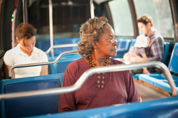 Elderly African-American woman riding a city bus.