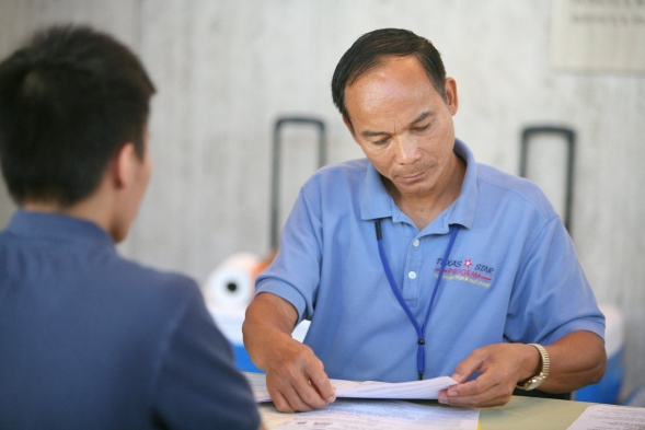 A man checks an application form completed by a young man.