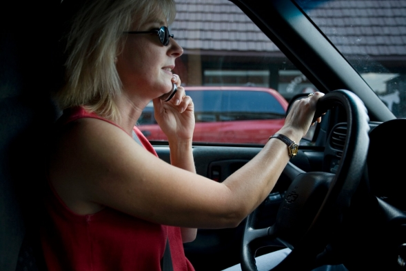 A woman talking on a cell phone as she drives a car.