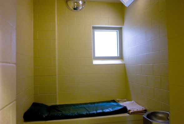 An empty cell, showing bed, window and sink.