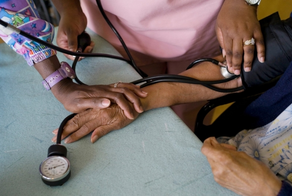 Two nurses take patient's blood pressure.