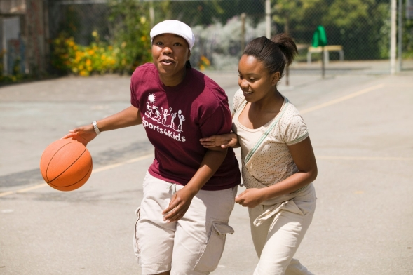 A coach plays basketball with a student in a school yard.