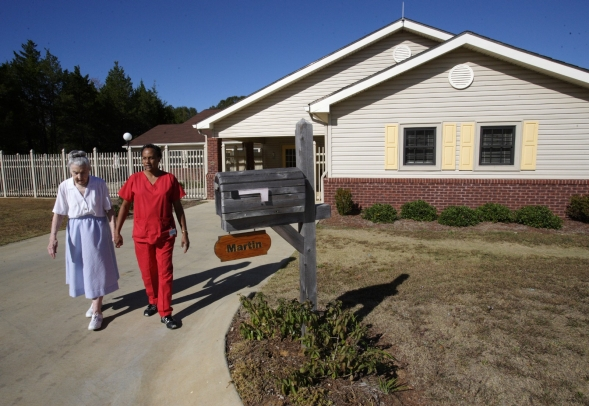 A nurses' aide and a nursing home resident walk together outside.