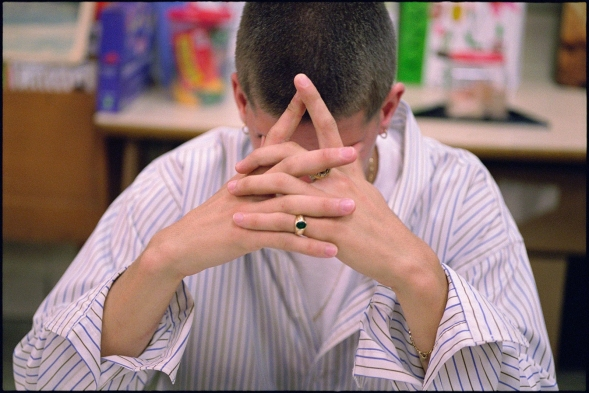 A high school student sits with his hands covering his face in a classroom.