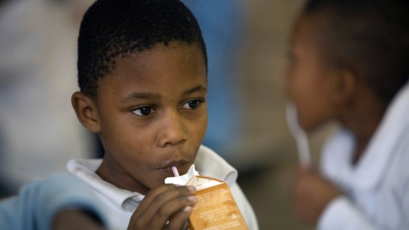 A boy drinking a carton of milk through a straw.