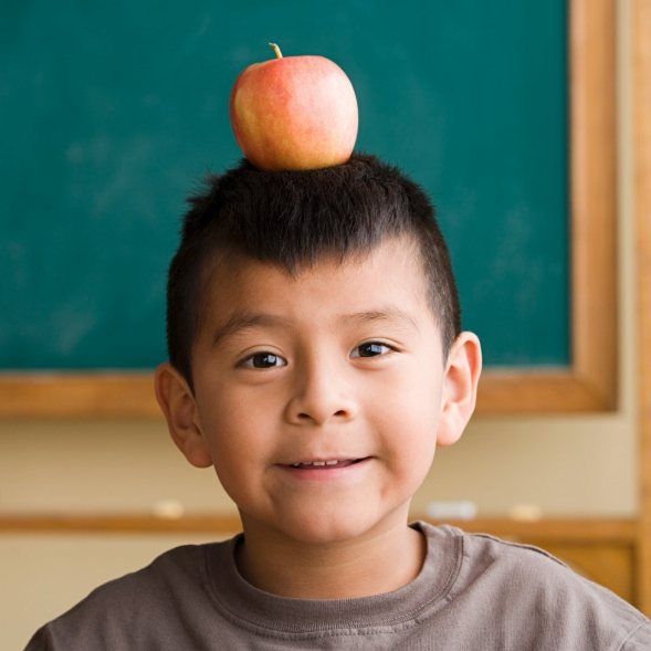 A boy standing in front of a chalkboard, balancing an apple on his head.