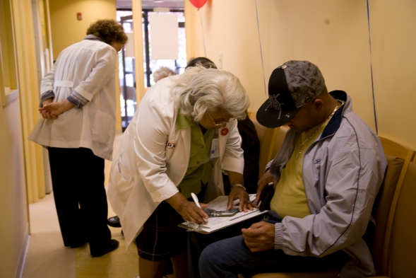 A health worker helps a member of the public complete forms at a polling station which offers flu shots.