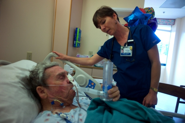 A nurse checks a hospital patient's breathing.