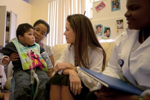 Two medical professionals talk with a disabled child who sits on his mother's lap.