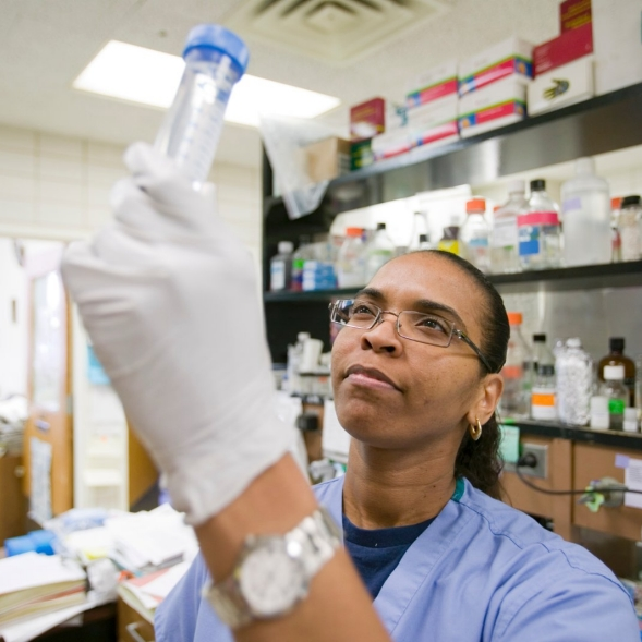 A resident in a university lab looks at a test tube.