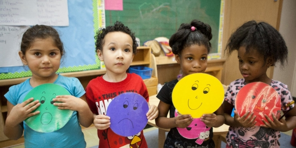 Students holding emotion masks.
