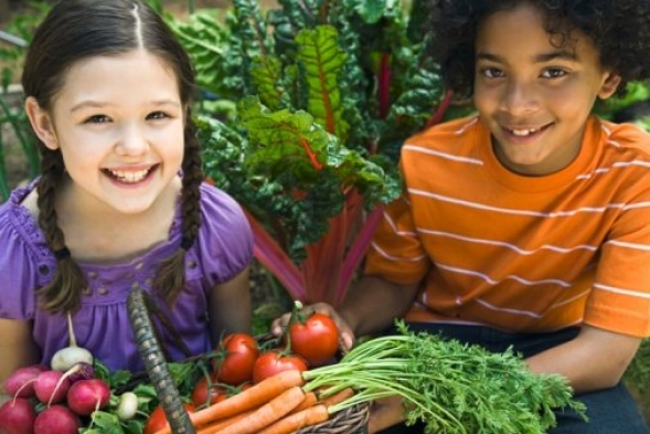 Smiling boy and girl holding a basket containing fresh produce.