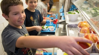 Three boys select healthy foods in an elementary school cafeteria lunch line.