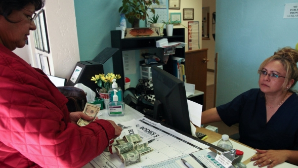 A patient pays a receptionist at a doctors office.