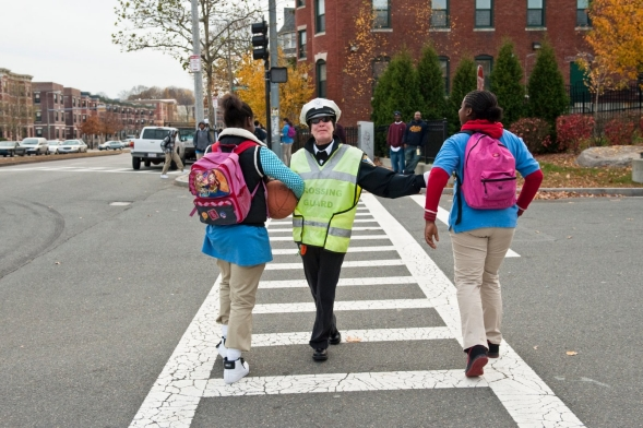 Crossing guard stopping traffic for kids at schools.