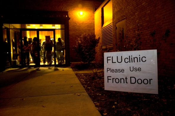 The front entrance of a polling center that offers flu vaccinations, at night.