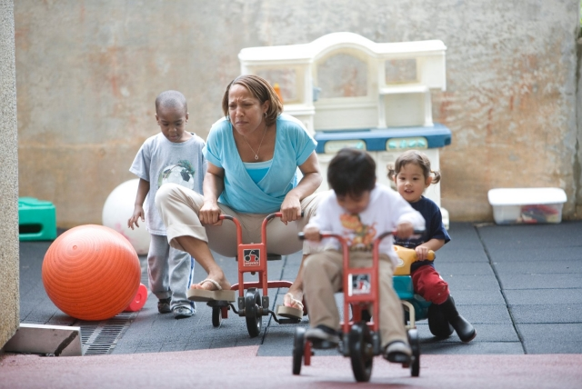 Preschool students and their teacher riding tricycles on playground.