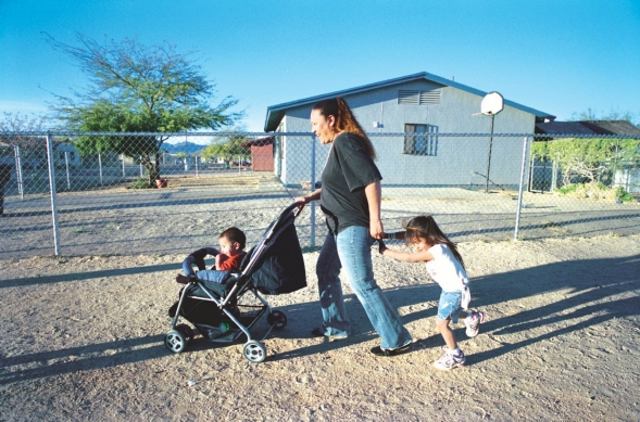 A woman pushes a stroller and holds a child's hand; walking in a residential area.
