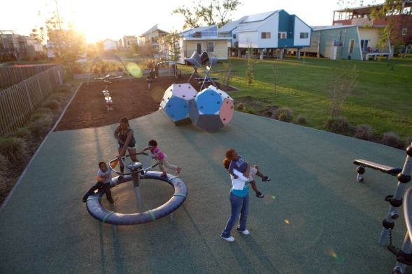 A family plays together on a community playground.