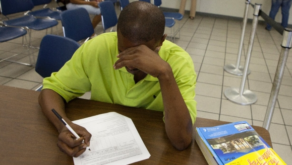 A man fills in a form at the reception area of a Department of Children and Family Serices office.
