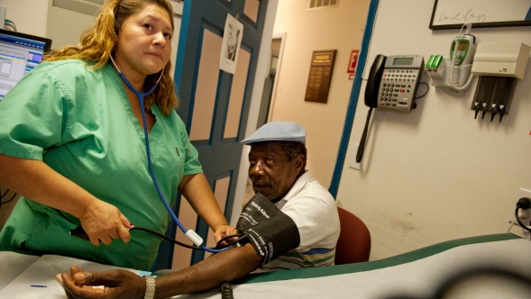 A nurse checks the blood pressure of a patient.