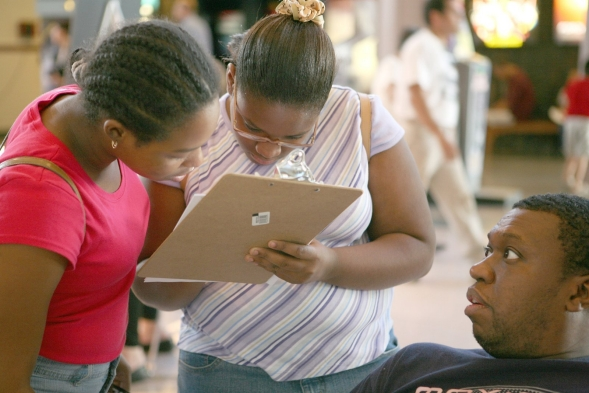 Two young women fill out an enrollment form.