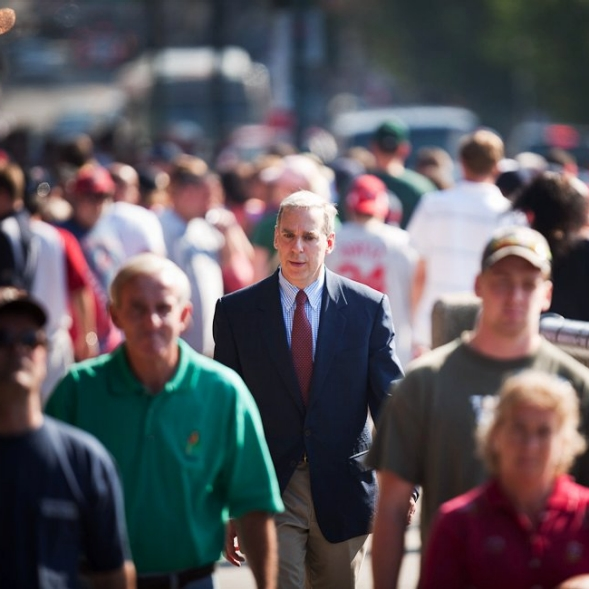 A professional man walking in a crowd along a city street.