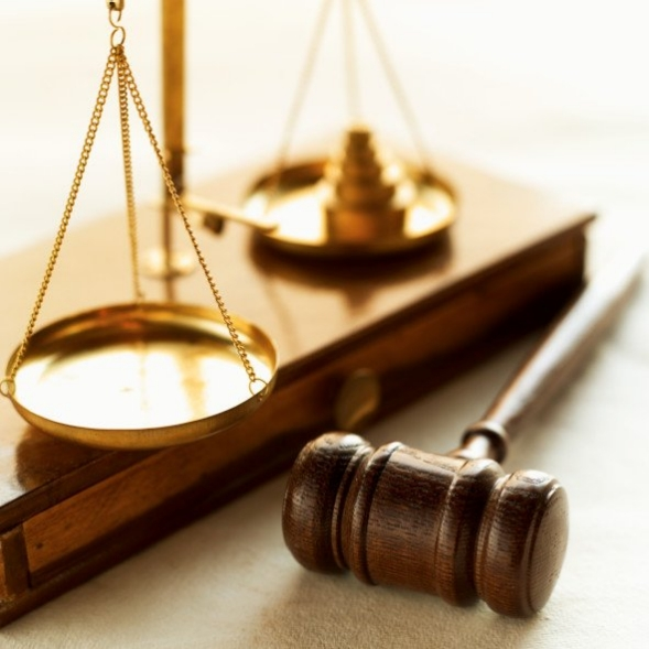 Weights balance scales of justice with a gavel beside it.