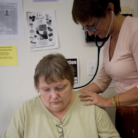 A nurse examines a patient with a stethoscope.