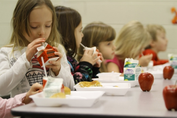Young girls enjoy a healthy lunch in their school cafeteria.
