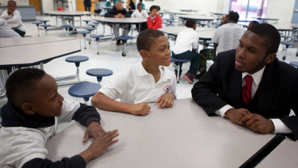 Male teacher speaks with young men of color in a cafeteria