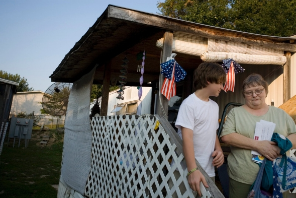 A woman talks to a child in the back yard of her trailer home.