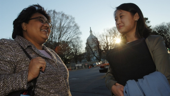Professionals talk outdoors in Washington, DC, with the Capitol Building in the background.