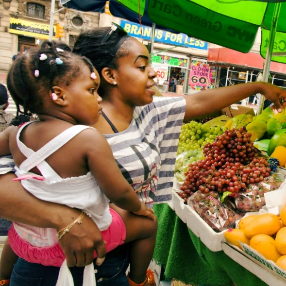 A woman and child pick fresh fruits and vegetables from a food cart.