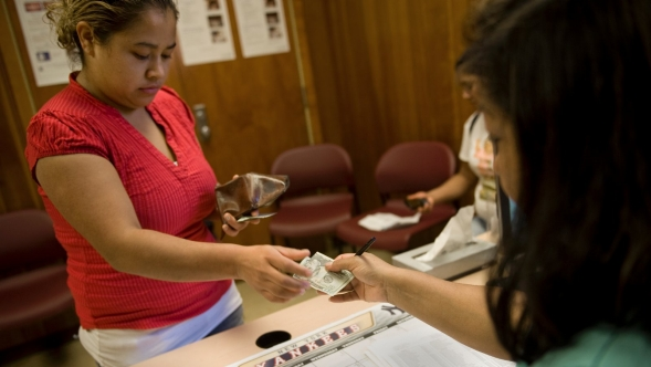A patient pays cash for services in a medical office.