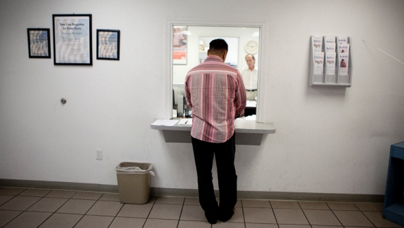 A man waits at the window of a reception area in a medicaid office.