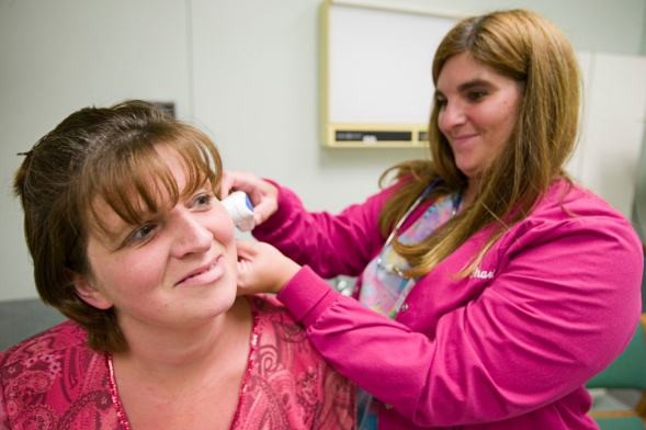 A medical assistant takes a patient's temperature.