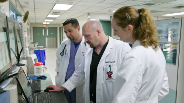 Three doctors in white coats look at a laptop screen in a hospital setting.