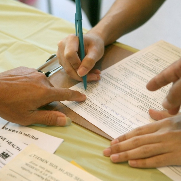 A man completes enrollment forms at a health care event.