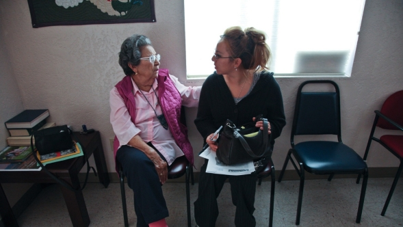 A woman and her daughter speak after filling out forms in a doctor's office waiting room.