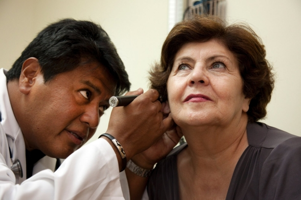 A doctor checks a patient's ears with an otoscope.